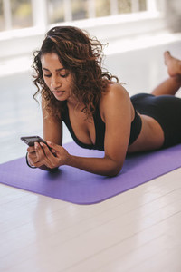Woman relaxing at yoga class with a cellphone
