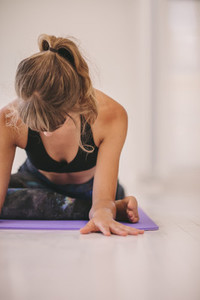 Woman doing stretching exercise on yoga mat