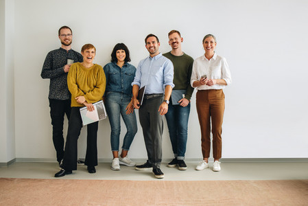 Happy colleagues standing against wall in office