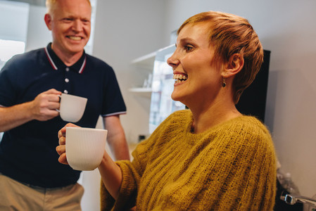 Business partners smiling during coffee break