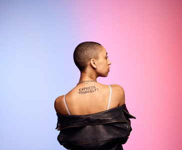 Shaved head woman with express yourself written on back