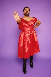 Gender fluid model in shiny dress singing in studio