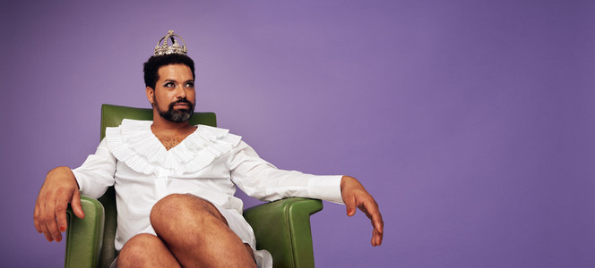 Attractive drag queen with crown sitting on his thrown