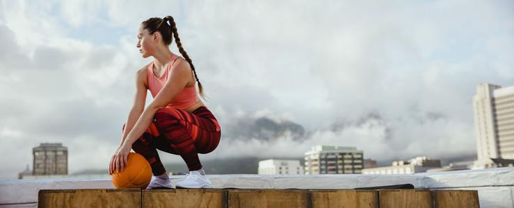 Sportswoman taking break from workout on rooftop