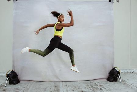 Female athlete in sportswear jumping midair