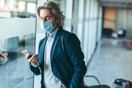 Business traveler with face mask waiting for his flight at airpo