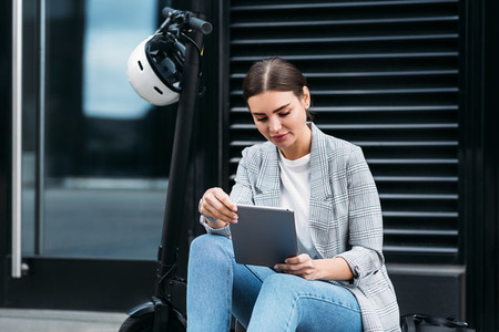 Beautiful caucasian female sitting on parked electric scooter on street holding a digital tablet