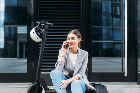 Young businesswoman sitting on an electric push scooter near a building and talking on mobile phone