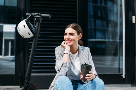 Beautiful smiling businesswoman with coffee sitting on an electric scooter at building looking away