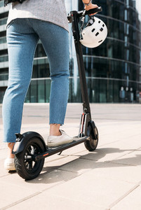 Cropped shot of unrecognizable businesswoman driving electric scooter in the city