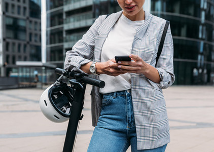 Cropped shot of businesswoman leaning on handlebar of electric scooter using an app for rent