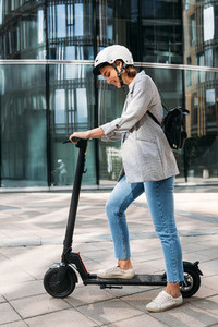 Young caucasian woman wearing cycling helmet standing outdoors with electric push scooter near glass building