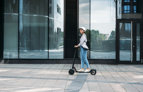 Young businesswoman wearing cycling helmet riding push scooter on footpath