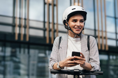 Cheerful woman in helmet using a mobile phone to unlock an electric scooter