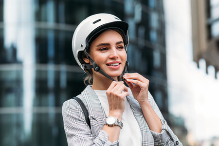 Beautiful woman in businesswear putting cycling helmet on a city street before a ride