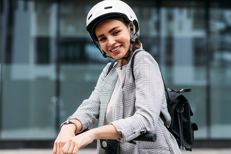 Portrait of cheerful businesswoman in white cycling helmet looking at camera leaning on handlebar of electric push scooter