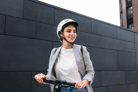 Smiling woman in helmet with an electric scooter at black wall looking away
