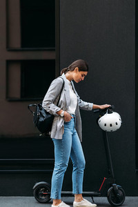 Full length shot of young businesswoman standing at a building with electric push scooter looking down