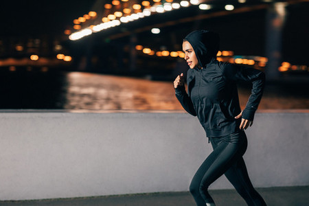 Young female athlete in hoodie sprinting at night in the city