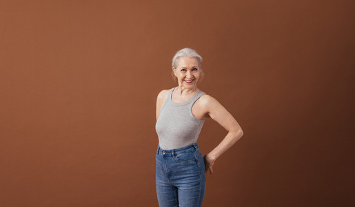 Portrait of a mature woman in casuals standing at brown background in studio