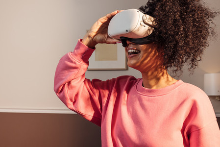 Cheerful woman in casuals standing indoors exploring virtual reality