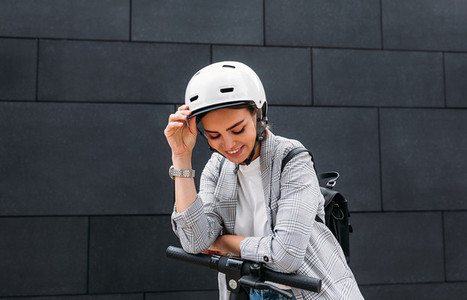 Happy businesswoman in cycling helmet leaning on handlebar of electric push scooter looking down