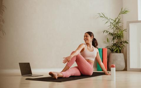 Woman doing yoga watching online class