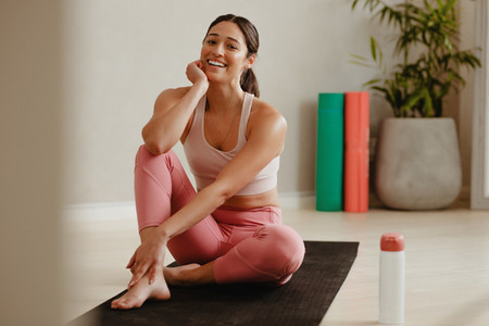 Woman taking a break from yoga session at gym
