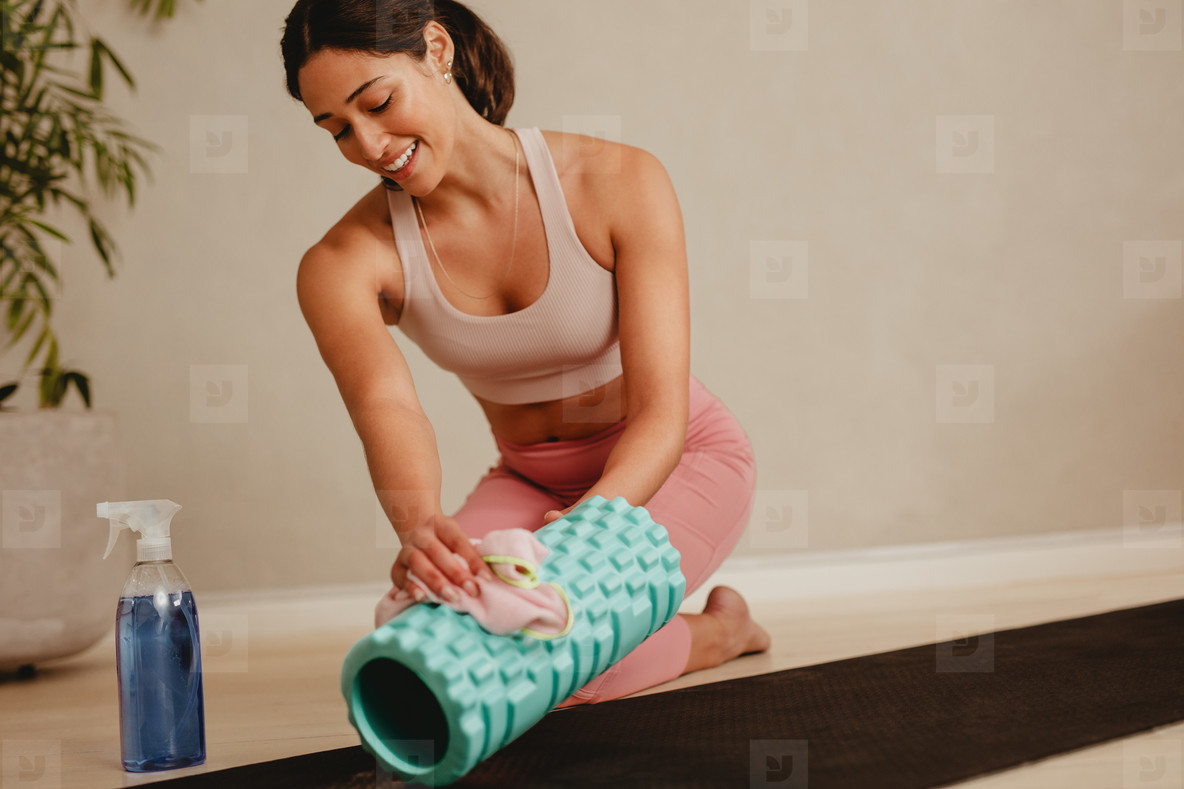 Woman sanitizing and cleaning gym equipment
