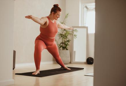 Woman doing yoga workout at fitness studio