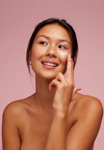 Beautiful woman applying moisturizer cream on her face