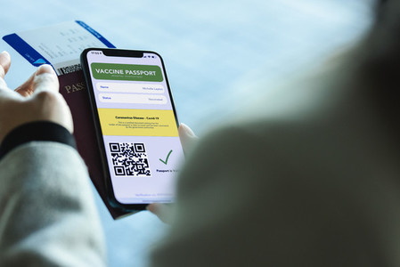 International traveler with vaccination passport on phone