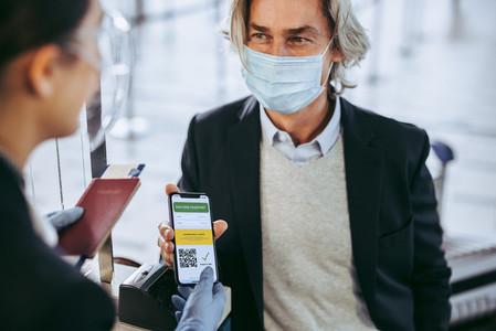 Businessman shows his vaccination passport to ground attendant