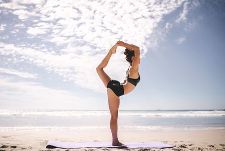 Woman doing Natarajasana yoga pose on the beach
