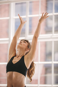 Woman with arms outstretched at yoga class