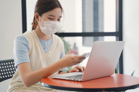 Young asian millennial woman wearing mask and using laptop and s