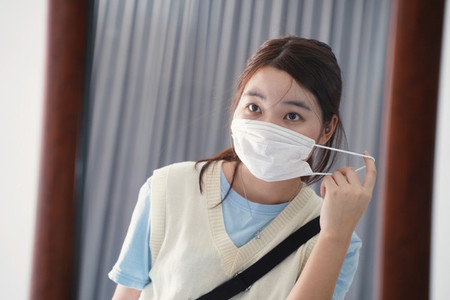 Young millennial asian woman wearing mask in front of mirror bef