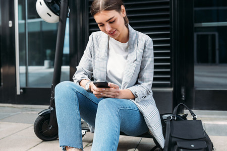 Businesswoman typing on a cell phone while sitting on electric push scooter at building