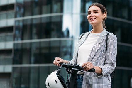 Smiling woman holding a handlebar of electric push scooter while standing at glass building