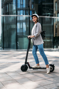 Young happy woman in casuals driving electric push scooter  Businesswoman in cycling helmet standing on e scooter