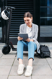 Young woman in casuals sitting on an electric scooter at building holding a digital tablet