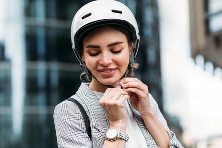 Cheerful caucasian woman wearing white cycling helmet preparing for ride