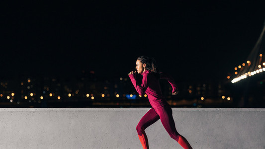 Young female jogger exercising in the evening  Woman running at embankment