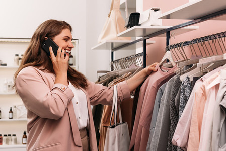 Smiling woman talking on cell phone while choosing clothes at rack in fashion store