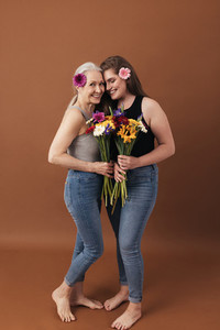 Two women with flowers posing in a studio a brown background