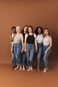 Studio shot of six women standing together holding their hands and looking at camera over brown background