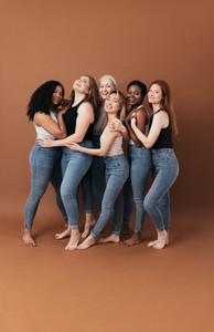 Group of cheerful women of different body type and ages standing together in a studio