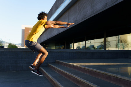 Black man doing squats with jumping on a step