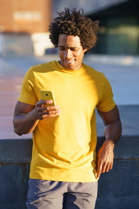 Black man consulting his smartphone while resting from his workout