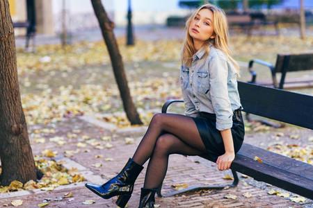 Blonde woman wearing denim shirt and black leather skirt sitting in an urban bench